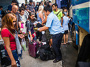 """03 JANUARY 2017 - BANGKOK, THAILAND:        People line up at Ekkamai Bus Station to get on a bus heading out of Bangkok. Travelers flocked to Bangkok bus and train stations Tuesday, the last day of the long New Year's weekend in Thailand. The New Year holiday in Thailand is called the """"seven deadly days"""" because of the number of fatal highway and traffic accidents. As of Monday Jan 2, 367 people died in highway accidents over the New Year holiday in Thailand, a 25.7% increase over the same period in 2016.    PHOTO BY JACK KURTZ"""