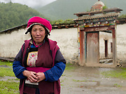 Portrait of a Tibetan woman wearing traditional clothing outside her home in a village near Zongdian (Shangri-La), Yunnan province, China.