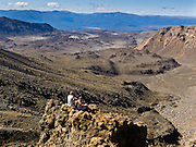 """Trampers (hikers) take a break in a volcanic wasteland. Tongariro National Park served as a location for fictional Mordor and Mount Doom in the """"Lord of the rings"""" Motion Pictures. In 1990 and 1993, UNESCO honored Tongariro National Park as a World Heritage Area and Cultural Landscape."""