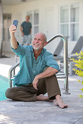 man sitting by a hotel pool taking a selfie