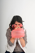 Young woman is breathing into a plastic bag. This technique is said to help reduce hyperventilation. The spasmophilia crisis caused by hyperventilation can be treated by breathing in a bag in order to increase the rate of carbon dioxide in the blood.
