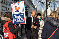"""© Licensed to London News Pictures. 21/01/2019. London, UK. People's Vote supporters Chuka Umuna MP (2-L) and Anna Soubry MP (3-L) walk past a pro-Brexit protester after leaving a meeting in the Cabinet Office. Prime Minister Theresa May will update MPs on her Brexit """"Plan B"""" this afternoon. Photo credit: Rob Pinney/LNP"""