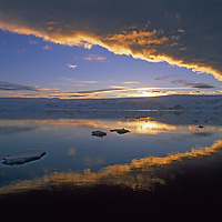 Dawn light illuminates clouds over Brabant Island & the Gerlache Strait in the Palmer Archipelago of Antarctica.