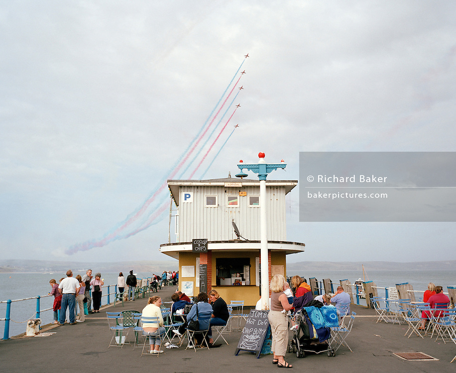 Spectators watch the Red Arrows, Britain's RAF aerobatic team displaying high above their heads during a public airshow.