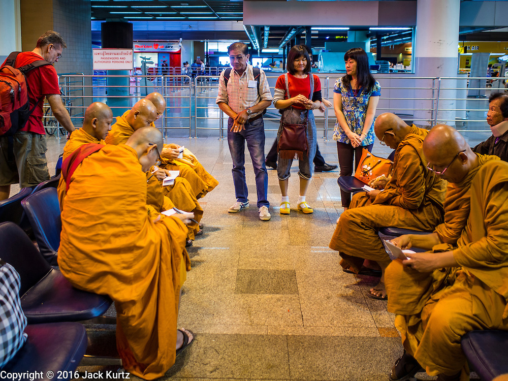 """23 FEBRUARY 2016 - BANGKOK, THAILAND: People talk to Buddhist monks in the departures lobby at Don Mueang International Airport. Nok Air, partly owned by Thai Airways International and one of the largest and most successful budget airlines in Thailand, cancelled 20 flights Tuesday because of a shortage of pilots and announced that other flights would be cancelled or suspended through the weekend. The cancellations came after a wildcat strike by several pilots Sunday night cancelled flights and stranded more than a thousand travelers. The pilot shortage at Nok comes at a time when the Thai aviation industry is facing more scrutiny for maintenance and training of air and ground crews, record keeping, and the condition of Suvarnabhumi Airport, which although less than 10 years old is already over capacity, and facing maintenance issues related to runways and taxiways, some of which have developed cracks. The United States' Federal Aviation Administration late last year downgraded Thailand to a """"category 2"""" rating, which means its civil aviation authority is deficient in one or more critical areas or that the country lacks laws and regulations needed to oversee airlines in line with international standards.        PHOTO BY JACK KURTZ"""