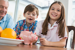 Two happy children and grandfather with piggy bank