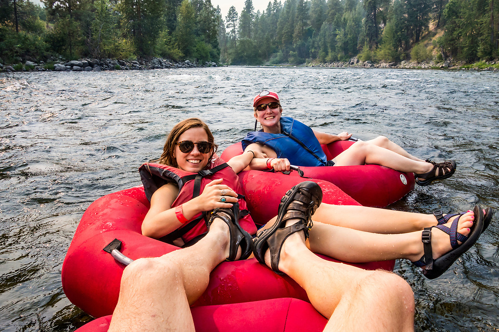 1st person point of view of two women and a man tubing down the Wenatchee river, Washington, USA.