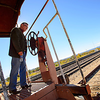102213  Adron Gardner/Independent<br /> <br /> Bob Clark, Grants/Cibola County Chamber of Commerce interim director, peeks over the rail of a decommissioned rail caboose in Grants Tuesday.