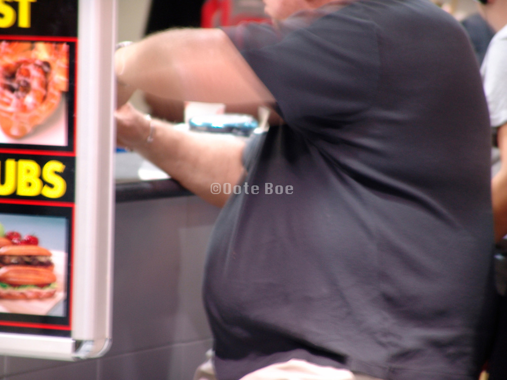 Close up of an over weight man while eating at the counter of a fast food restaurant.