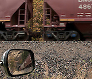 As seen in a rear view mirror, a train of grain hoppers emerges from a tunnel and passes by on it's way through the Columbia River Gorge, Washington, USA.