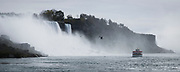 SHOT 10/21/17 1:32:07 PM - Seagulls fly around the American Falls in Niagara Falls, N.Y. as a Maid of the Mist boat passes by. The American Falls is the second-largest of the three waterfalls that together are known as Niagara Falls on the Niagara River along the Canada–U.S. border. Unlike the much larger Horseshoe Falls, of which two-thirds is located in Ontario, Canada and one-third in the U.S. state of New York, the American Falls is entirely within the United States. Located on the Niagara River, which drains Lake Erie into Lake Ontario, the combined falls form the highest flow rate of any waterfall in North America that has a vertical drop of more than 165 feet (50 m). During peak daytime tourist hours, more than six million cubic feet of water goes over the crest of the falls every minute. Horseshoe Falls is the most powerful waterfall in North America, as measured by flow rate. Niagara Falls is famed both for its beauty and as a valuable source of hydroelectric power. The falls are 17 miles (27 km) north-northwest of Buffalo, New York. Buffalo, N.Y. is the second most populous city in the state of New York and is located in Western New York on the eastern shores of Lake Erie and at the head of the Niagara River. By 1900, Buffalo was the 8th largest city in the country, and went on to become a major railroad hub, the largest grain-milling center in the country and the home of the largest steel-making operation in the world. The latter part of the 20th Century saw a reversal of fortunes: by the year 1990 the city had fallen back below its 1900 population levels. (Photo by Marc Piscotty / © 2017)