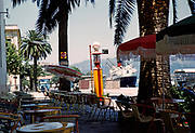 Ferry ship in harbour seen from port waterfront cafe bar, Calvi, Corsica, France in late 1950s