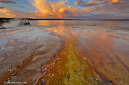 Colorful mineral deposits emit from Black Pool geyser in the West Thumb Geyser Basin along Yellowstone Lake in Yellowstone National Park in Wyoming at sunset
