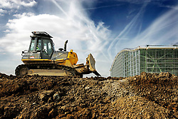 Heathrow Airport, T5 construction site, bulldozer on eath mound, main terminal building in background, 22 March 2006, Ref CHE03628d, SB