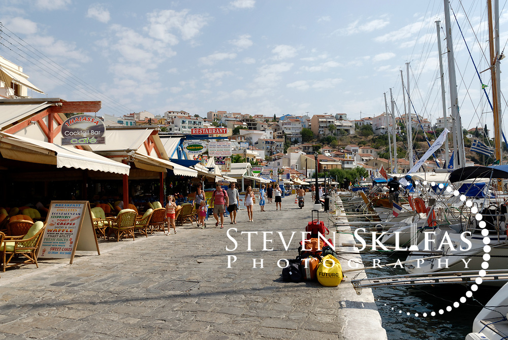 Samos. Greece.  View along the Pythagoreio waterfront which is filled with restaurants and cafes and has colourful fishing boats docked in its pretty harbour