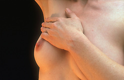 Woman examining breast checking for tumorous growths,