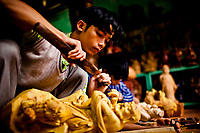 A young man carves a wooden statue at Tan An shop in Hoi An's Old Town in Vietnam. From the craft village of Kim Bong, Tan An brings the village's wood carving art to Hoi An.