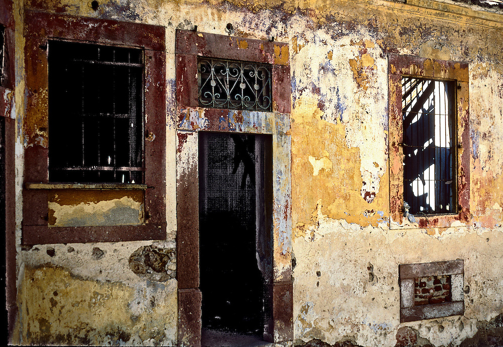 The facade of the house, built of stone with walls coated in painted plaster, forms a desolate and somehow compelling graphic geometry in dark red, yellow, and cream colors.  The interior seems ruined though the exterior has presence.