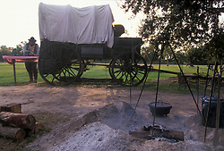 Cowboy standing beside an old western wagon and extinguished fire at a campsite