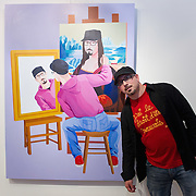 VENICE, ITALY - JUNE 01:  Artist Giuseppe Veneziano stands in front of hos portrait at Galleria Contini on June 1, 2011 in Venice, Italy. Veneziano's controversial paintings portray  pop culture icons and historical figures.