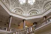 The Muses Stair and glass octagonal lantern, in the Foreign and Commonwealth Office FCO, on 17th September 2017, in Whitehall, London, England. The roof is graced by goddesses of plenty canephora and cherubs illustrating the Roman virtues. The main Foreign Office building is in King Charles Street, and was built by George Gilbert Scott in partnership with Matthew Digby Wyatt and completed in 1868 as part of the new block of government offices which included the India Office and later 1875 the Colonial and Home Offices. George Gilbert Scott was responsible for the overall classical design of these offices but he had an amicable partnership with Wyatt, the India Office's Surveyor, who designed and built the interior of the India Office.