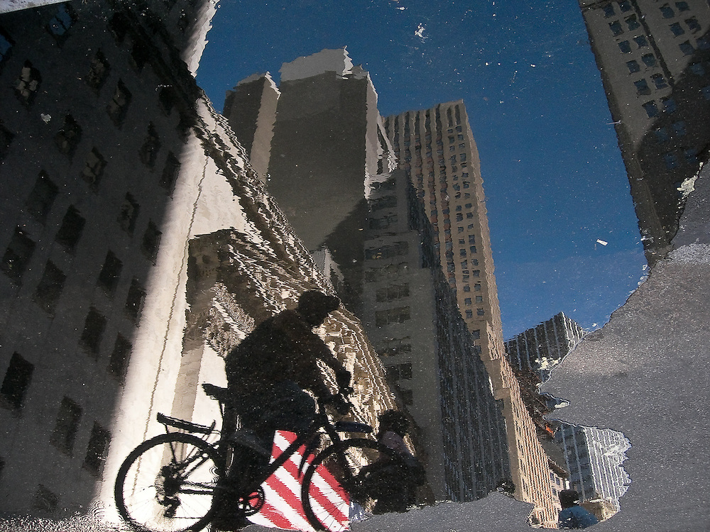 Reflection in a puddle of a biker in Wall Street, New York