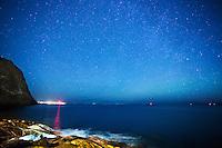 Rød lys fra fyret på Alnes speiler seg under en stjerneklar himmel.<br /> Foto: Svein Ove Ekornesvåg