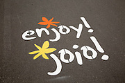 Enjoy and Joio English and Welsh languages writing on path, Swansea, West Glamorgan, Wales, UK