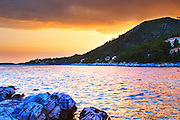 The Brna bay at sunset, bright orange sky, cliffs in foreground, sky reflected in the sea water. Holiday homes on the hillside. Prizba village. Korcula Island. Prizba, Riva Apartments, Danny Franulovic. Korcula Island. Dalmatian Coast, Croatia, Europe.