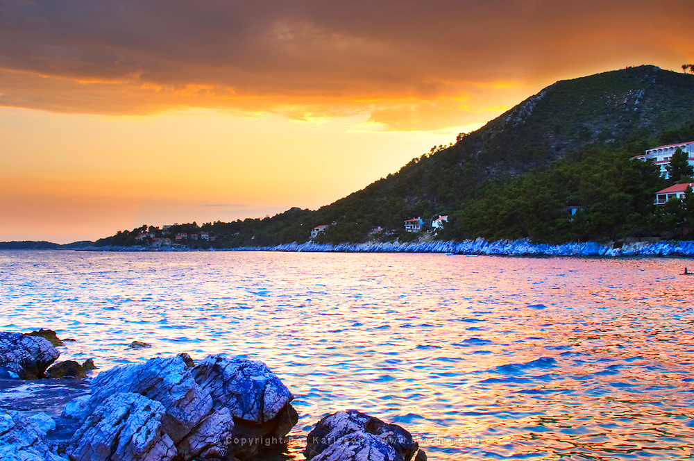 The Brna bay at sunset, bright orange sky, cliffs in foreground, sky reflected in the sea water. Holiday homes on the hillside. Prizba village. Korcula Island. Prizba, Riva Apartments, Danny Franulovic. Korcula Island. Dalmatian Coast, Croatia, Europe.