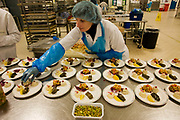 "A lady employee of the world's largest independent provider of airline catering and provisioning services, Gate Gourmet, reaches out to add the last items in the company's factory on the southern perimeter road at Heathrow Airport, West London. Gate Gourmet serve more than 200 million meals on 2 million airline flights a year to their 250-plus airline customers at more than 100 airport locations around the globe. Apart from creating the bespoke meals for an airline's culture and ethnic demands, that pack the pre-flight carts, deliver and load into the aircraft galleys and afterwards, they dispose of the waste and strip, wash and sterilize the equipment. From writer Alain de Botton's book project ""A Week at the Airport: A Heathrow Diary"" (2009)."