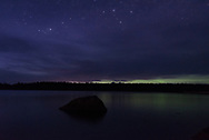 An early summer night creates a surreal scene as the northern lights show just through a sliver of clouds.
