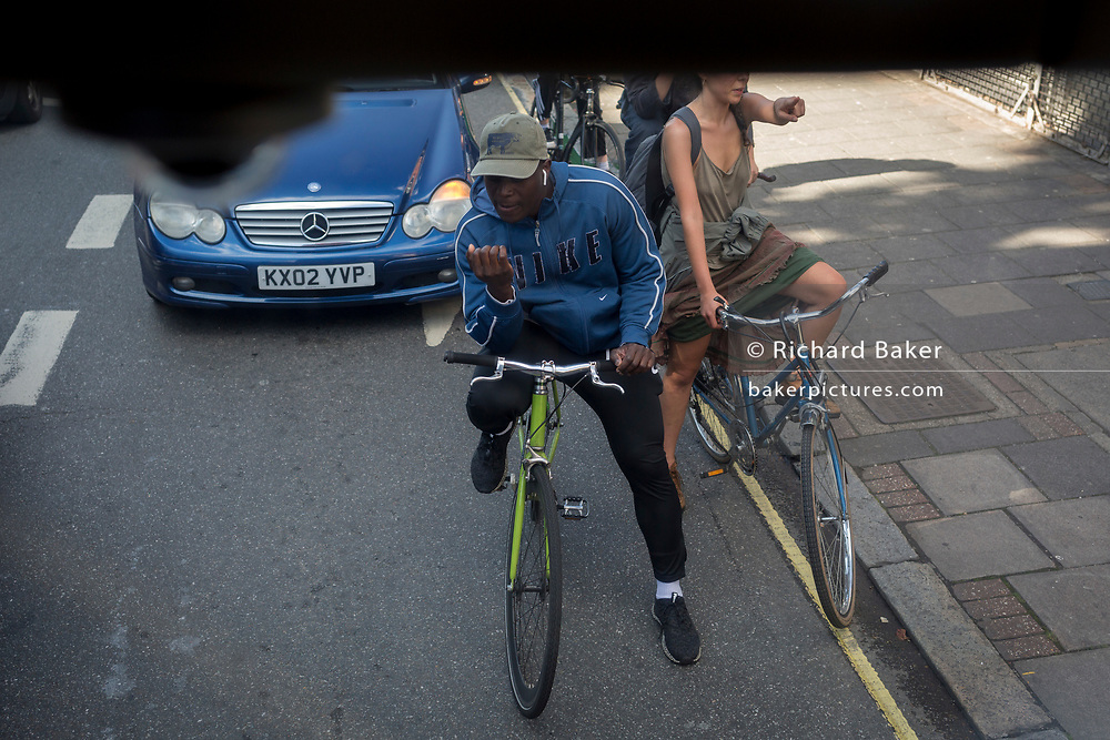 Cyclists wait for the lights to change while riding along the Walworth Road in Southwark, on 15th June 2019, in London, England.