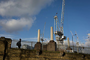 A local man walks past on-going construction work in Battersea, surrounding Battersea Power Station, on 22 January 2018, in south London, England.