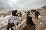 With horse and yak caravan, fighting the wind. Between Ech Keli and Burgut Yor camp...Trekking through the high altitude plateau of the Little Pamir mountains, where the Afghan Kyrgyz community live all year, on the borders of China, Tajikistan and Pakistan.