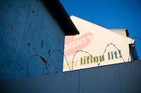 "An alley in 101 Reykjavík. Barbed wire on a wall, old advertisement for Icelandic paint Harpa in background. Their slogan says: ""Harpa gives color to life"". Gaddavír við bakhús Fáfnis mótorhjólaklúbbs. Harpa gefur lífinu lit á vegg í baksýn."