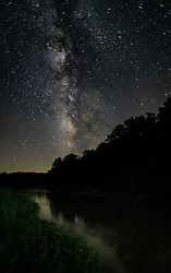 The Milky Way rises above the Eleven Point River shortly after sunset.<br /> <br /> The 138-mile-long Eleven Point River flows from southern Missouri into northern Arkansas. Its flow more than doubles from Greer Spring, adding over 200 million gallons of water per day. According to U.S. Geological Survey, the name comes from the French word pointe, a wooded point of land marking a river bend. French Voyageurs marked distance counting these points of river bends.<br /> <br /> A 44 mile section of the river was established in 1968 as The Eleven Point National Wild and Scenic River. The picturesque river is one of the eight initial units of the National Wild and Scenic River system. This designation created a shoreline that is mostly undeveloped.<br /> <br /> Paddling is a popular activity on the river for kayakers and canoeists with intermediate skills (Class I and Class II). The river alternates between deep clear pools and rapids. Also popular is fishing with smallmouth bass, rock bass, walleye and trout being among the fish sought out by anglers.<br /> <br /> Unlike the nearby Current and Jacks Fork Rivers, the Eleven Point River does not have as many gravel bars making river camping more challenging.<br /> <br /> The 4,167-acre Eleven Point State Park near the historic Pigman Ranch was announced in 2016 but remains undeveloped due to a legal dispute over the legality of the easement of the park on the river.