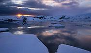 Sunburst sunrise glows ever so gracefully over the tranquil Jökulsárlón Glacier Lagoon in Iceland.