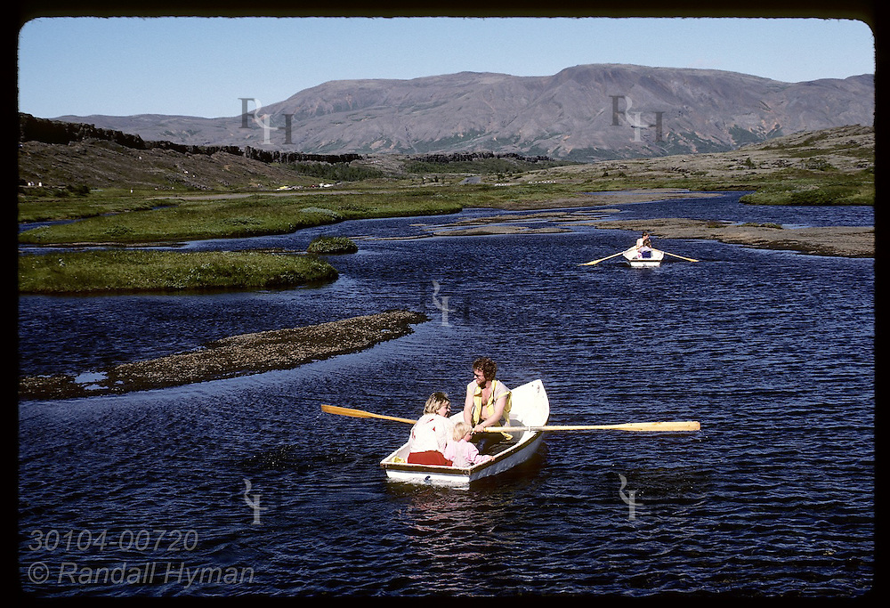 Tourists row rental boats along Oxara river @ Thingvellir, first site of world's oldest parliamnt Iceland