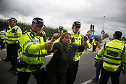 Anti-fracking  activists and protesters outside the gates of Quadrillas fracking site June 31st, New Preston Road, Lancashire, United Kingdom.  As a truck with equipment arrives police move in to clear the road. The struggle against fracking in Lancashire has been going on for years. The fracking company Quadrilla is finally ready to bring in a drill tower to start drilling and anti-frackinhg activists are waiting in front of the gates to block the equipment getting in. Fracking is a destructive and potential dangerous and highly contentious method of extracting gas and this site will be the first of many in the United Kingdom reaching miles out under ground.