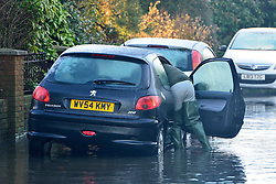 © Licensed to London News Pictures. 12/01/2014. Wraysbury, UK. A man checks his car. Flooding in Wraysbury, Berkshire today 12th January 2014.  Flooding and property damage is expected to continue along the River Thames.  Large areas of Britain are experiencing flooding after wet weather. Photo credit : Stephen Simpson/LNP