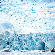 Tourists in a Zodiac inflatable boat cruise past steep cliffs of ice from a glacier on the shore at Curtis Bay on the Antarctica Peninsula.