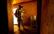 A soldier searches a house for weapons cache and people who are on the blacklist.