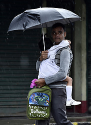 May 4, 2019 - Barpeta, India - A man retrning his child after school during a rainfall due to the cyclone Fani, in Barpeta, Assam, India on Saturday, May 4, 2019. Cyclone Fani, an extremely severe cyclonic storm, barreled through Odisha causing widespread destruction and eight reported deaths. The India Meteorological Department (IMD) said it would continue to move north-north-east over land and weaken further into a severe cyclonic storm. (Credit Image: © David Talukdar/NurPhoto via ZUMA Press)