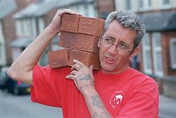 Builder carrying pile of bricks on shoulder,