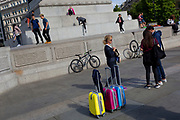 Coloured suitcases as young tourists play on the plinth of Nelson's Column in Trafalgar Square, on 10th August 2017, in London, England.