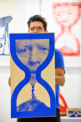 © Licensed to London News Pictures. 05/10/2019. LONDON, UK. Artist Savvas Verdis holds up one of his giant rubber stamps depicting Boris Johnson, Prime Minister, within an hourglass at The Other Art Fair, presented by Saatchi Art.  120 international, independent artists are displaying their works to be sold direct to buyers.  The fair is taking place at Victoria House in Bloomsbury until 6 October 2019.  Photo credit: Stephen Chung/LNP