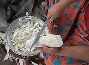 Shaving Cassava, also known as Manioc. With plantain, it is the main source of food carbohydrates for Tsimane. The Nate family spends time under the opened kitchen hut.