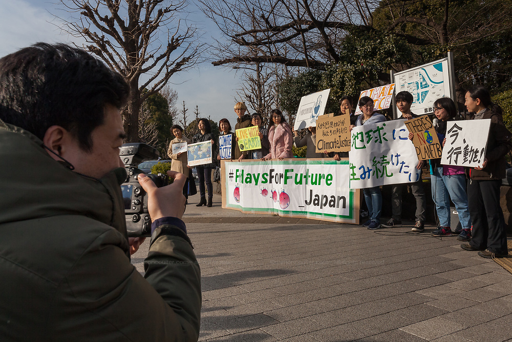 """A photographer for the media shoots a group of mostly young Japanese people take part in a demonstration as part of the """"Fridays for Future"""" movement outside the National Diet Building in Tokyo, Japan. Friday February 22nd 2019. Around 30 people took part in the demonstration in which started at 3pm. The Glbal Strike for Future was started by Swedish school student, Greta Thunberg who began striking from her school to demand adults do something about climate change to ensure the furture she was studying for. Since then thousands of strikes have taken place around the world. This was the first such strike in Japan and though no school students left their schools to take part the organisers hope the Global Strike for Future on March 15th will attract many young people in Japan"""