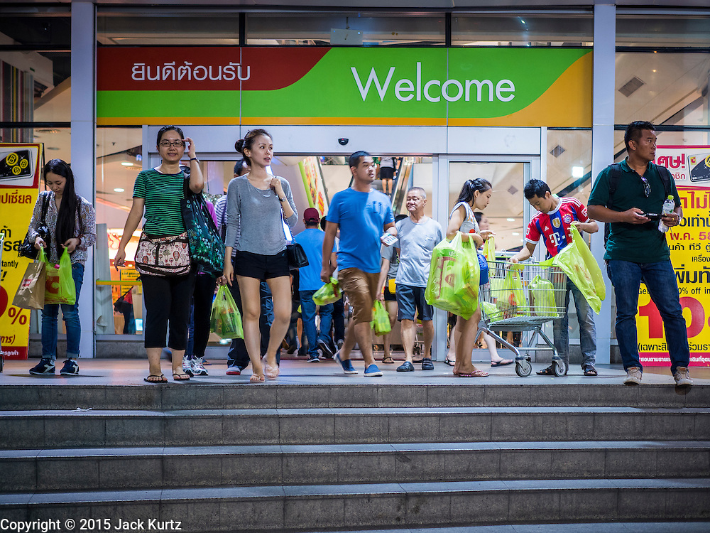 20 MAY 2015 - BANGKOK, THAILAND: Shopper leave the Big C Supercenter on Ratchadamri Road in Bangkok. Bangkok's malls consume more electricity than some provinces. Siam Paragon, a popular high end mall in central Bangkok, consumes nearly twice as much electricity at the northern province of Mae Hong Son. Thais and foreigners alike flock to the malls in Bangkok, which are air conditioned. Most of the electricity consumed in Bangkok is generated in Laos and Myanmar. In 2013, the Bangkok Metropolitan Region consumed about 40 per cent of the Thailand's electricity, even though the BMR is only 1.5 per cent of the country's land area and about 22 per cent of its population.   PHOTO BY JACK KURTZ